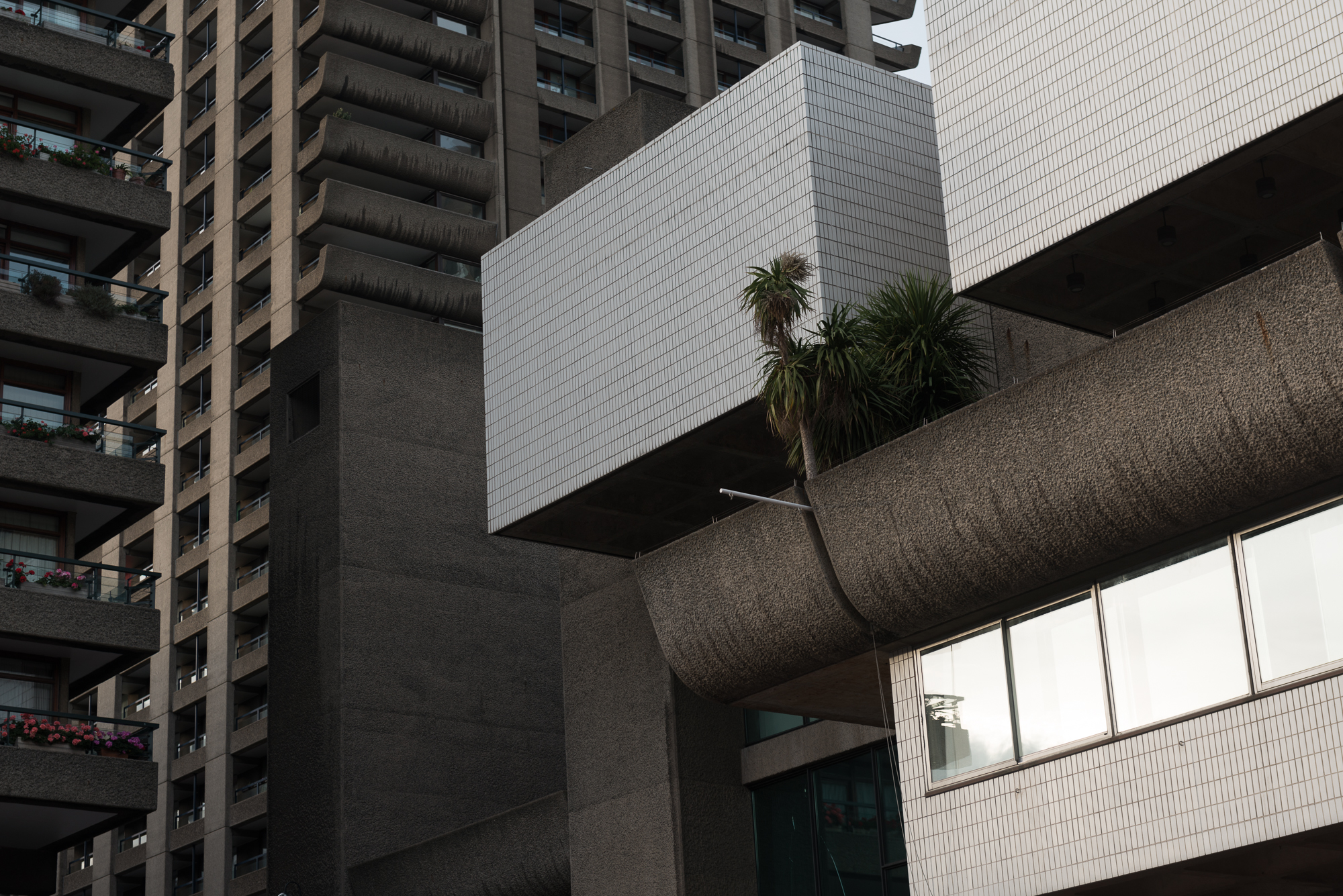 A photo of the a corner of The Barbican Centre with several tower blocks in the background.