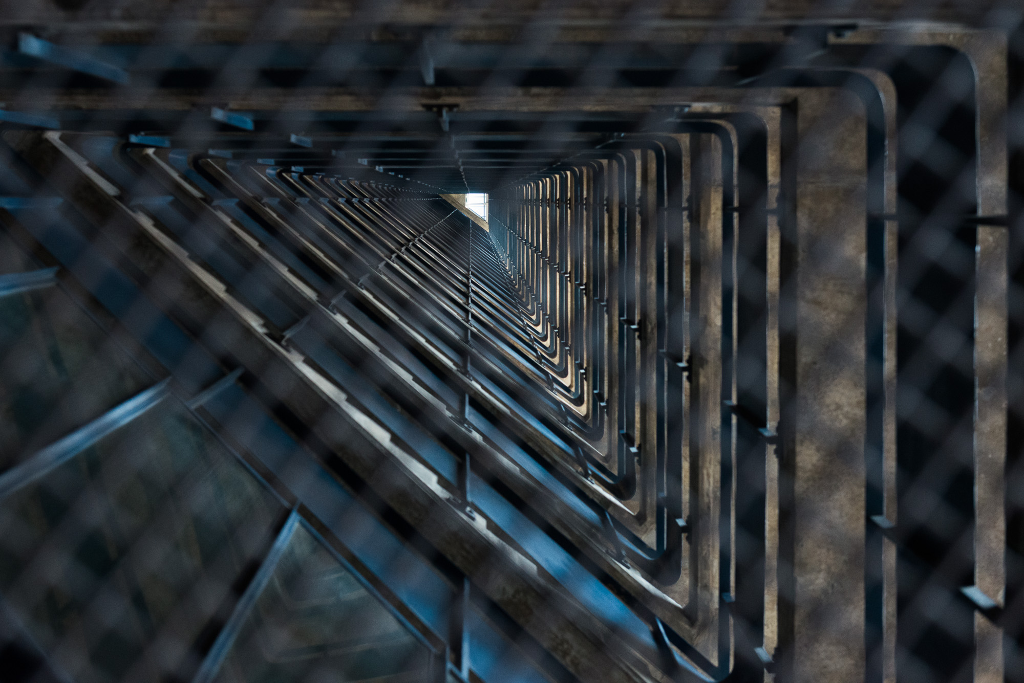 Looking up the void of a staircase through a metal grate. The void is triangular.