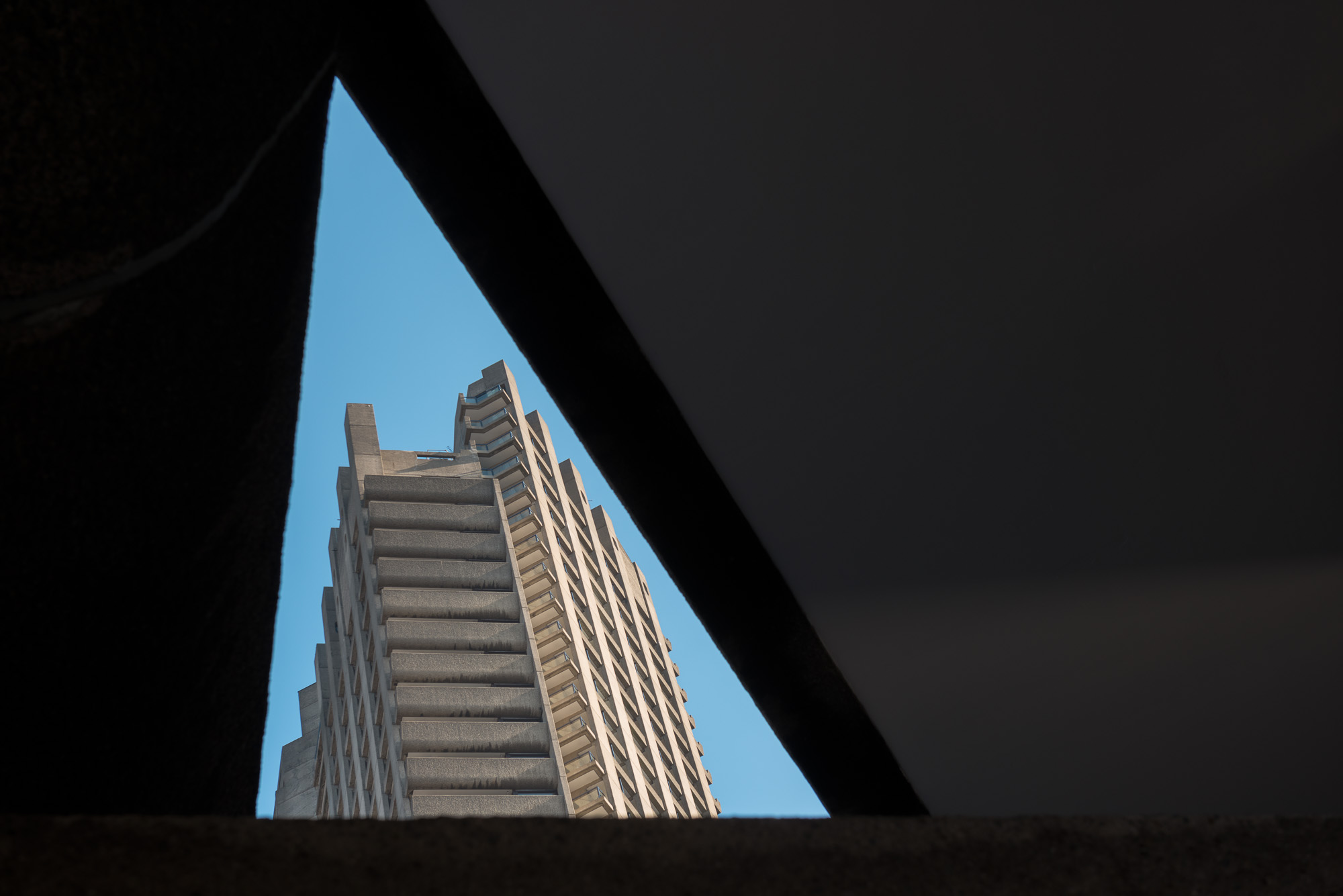 Looking up through a void in a roof, forming a triangle of sky. Framed in the sky is the top of a tower block in the Barbican, which also forms a triangle shape.