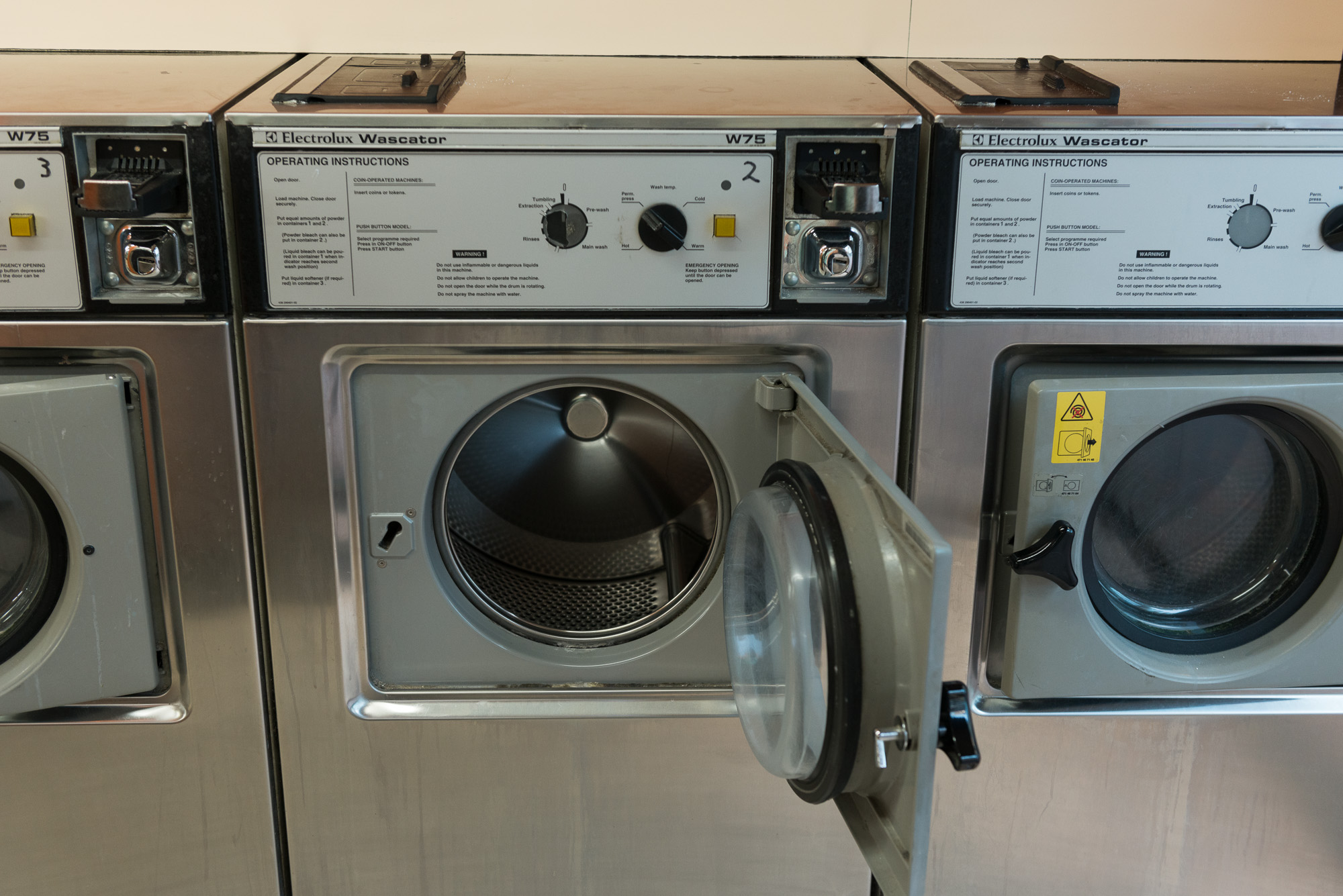 A photo of a several washing machines in a laundromat. The one immediately in front of the camera has its door open.