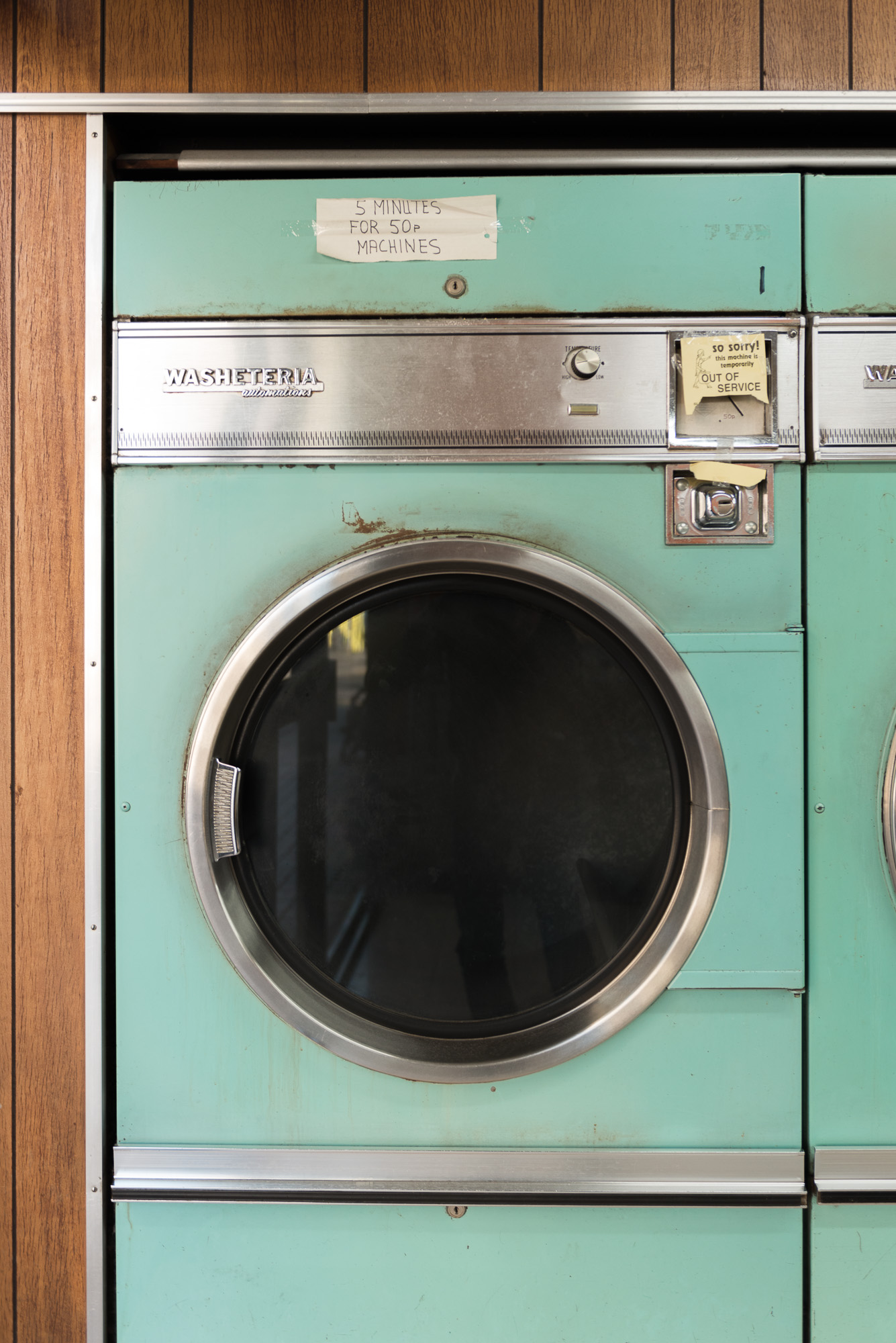A photo of a vintage washing machine in a laundromat.