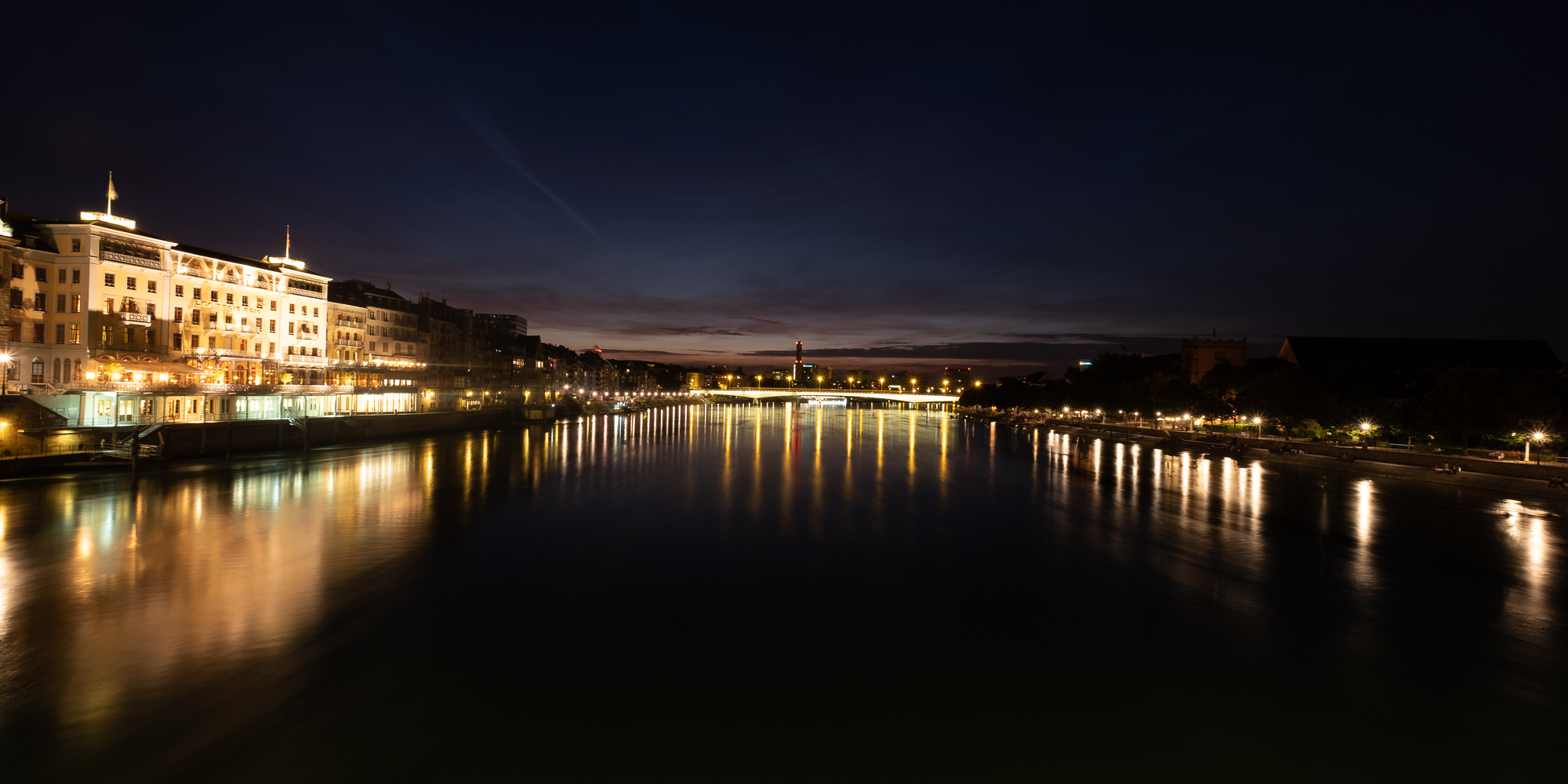A panorama taken from a bridge over the Rhine at nighttime. There are buildings in the distance lit up and lights reflected in the water.