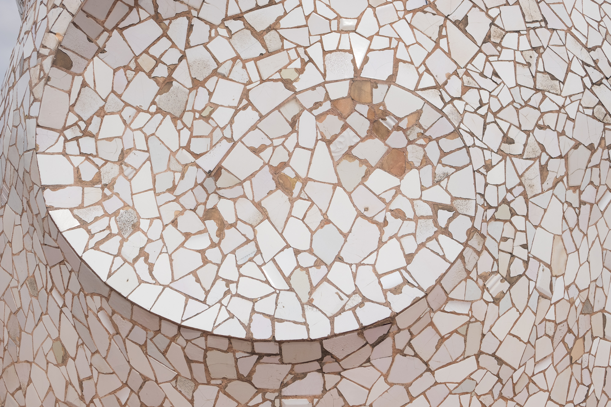 A close photo of a mosaic at Casa Milà. The tiles are roughly broken and all white - they're arranged in a spiral pattern.