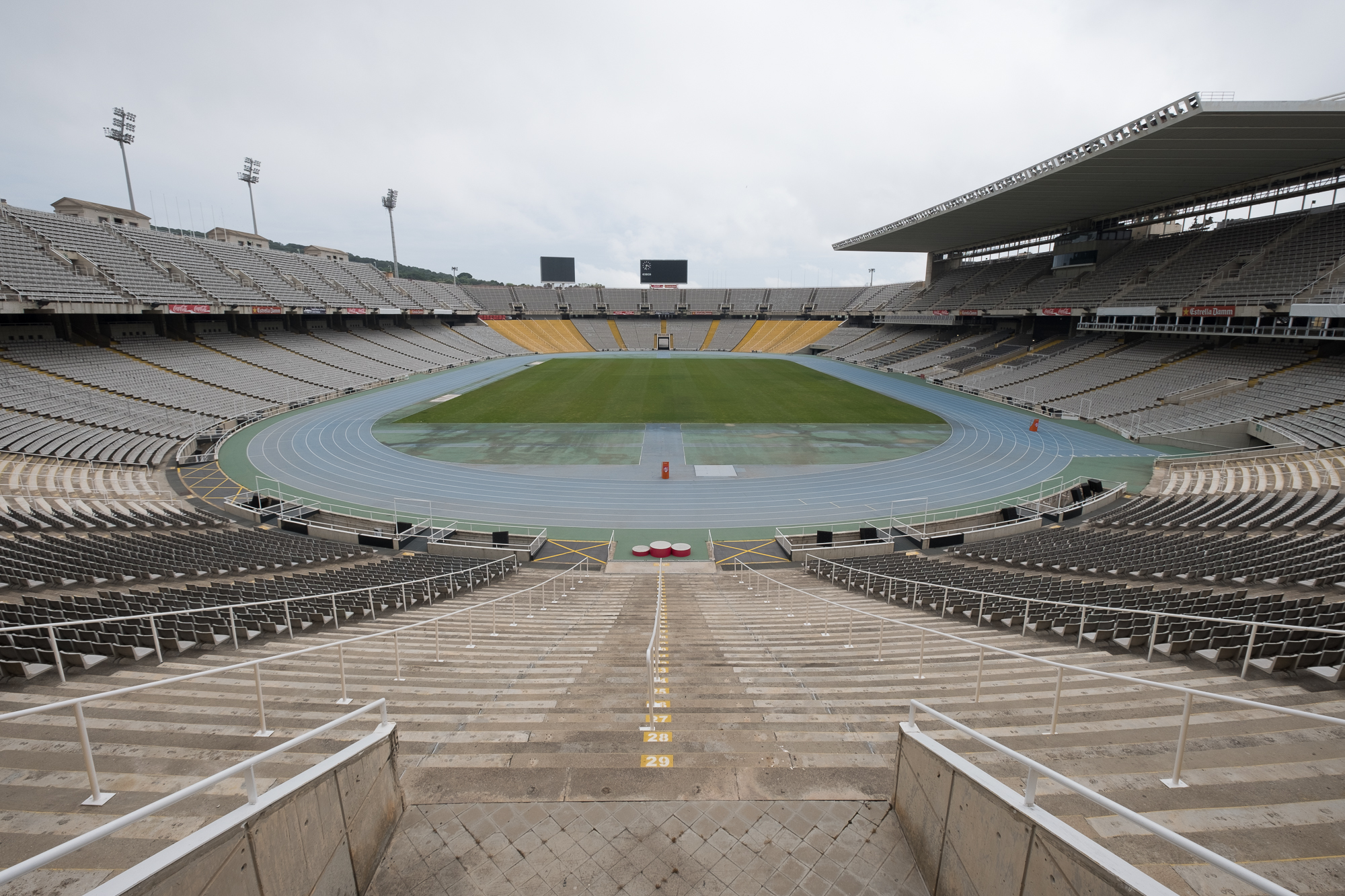 A photo of the olympic stadium in Barcelona. The photo is taken from one end, looking in to the main arena. There are seats all around and the playing field in the centre.