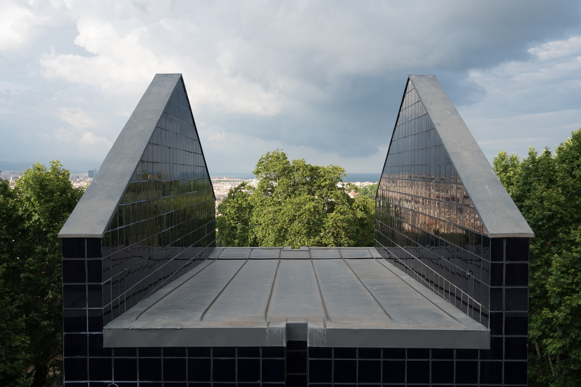 An open air photo of two tiled walls. They're perpendicular to each other and each end is slanted like the roof of a building.