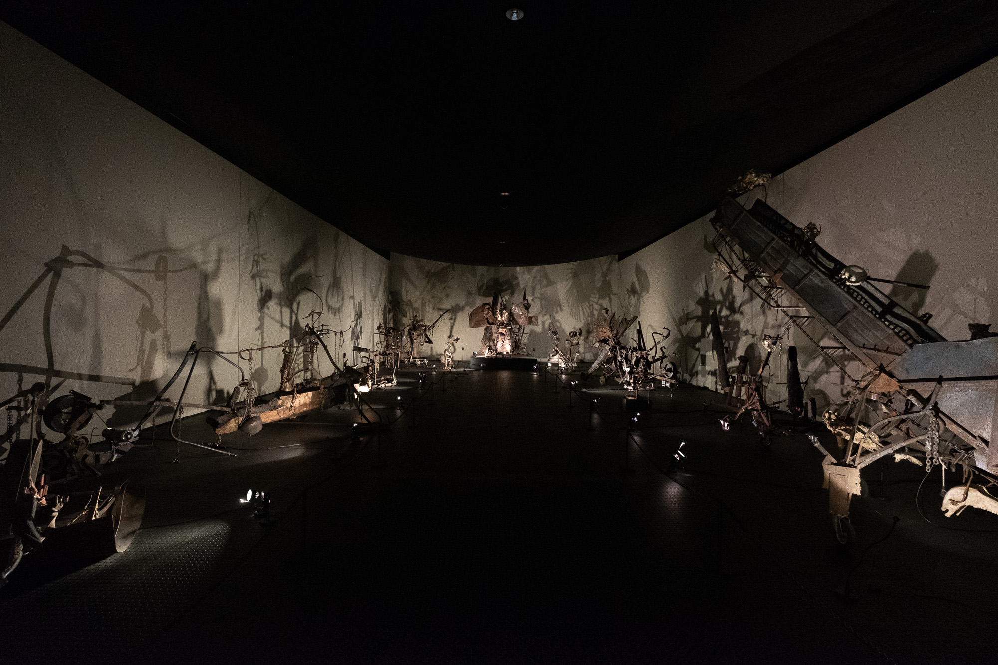 A dark room filled with many eery metallic sculptures by Jean Tinguely.
