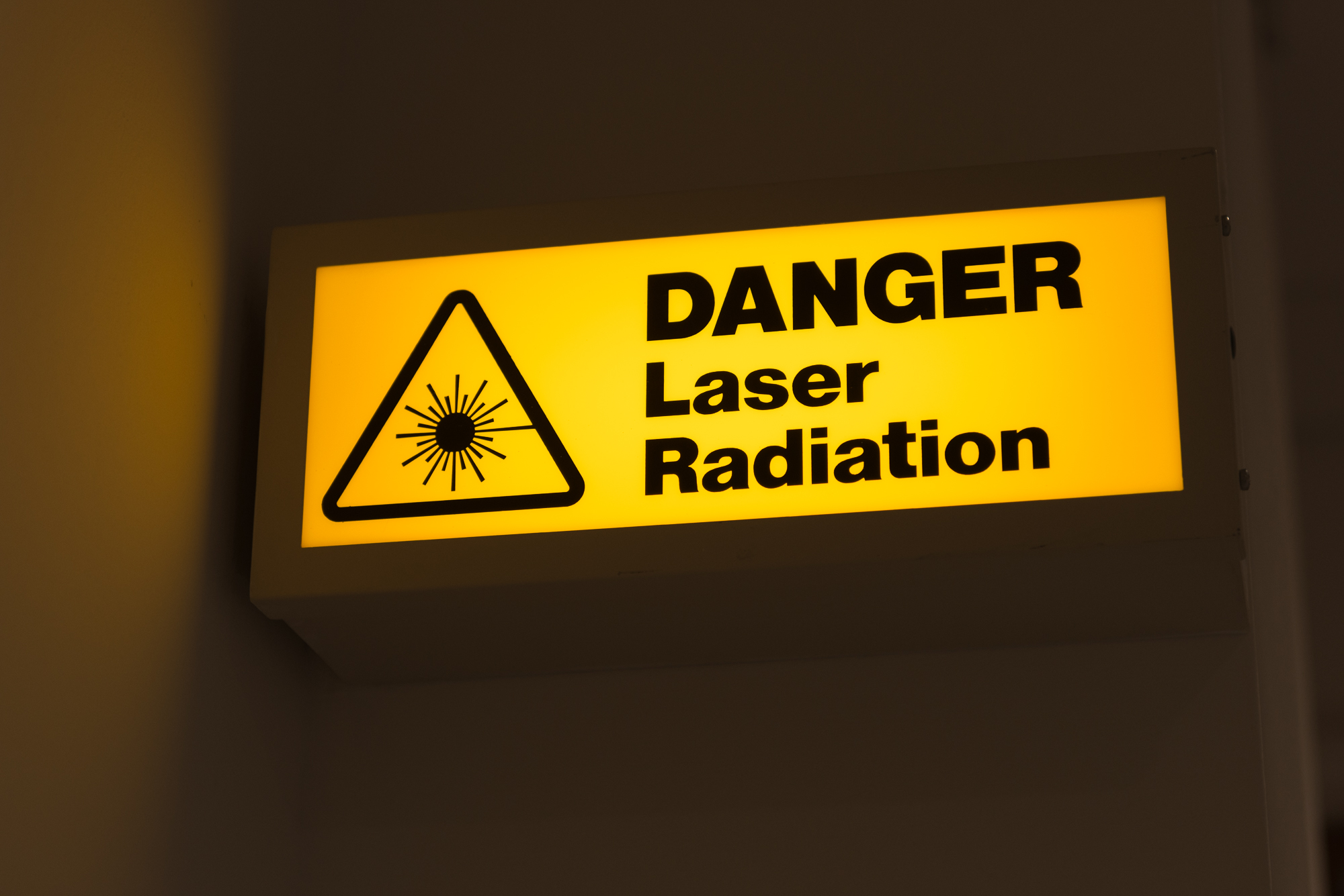 A photo of a lit sign that reads 'Danger - laser radiation'