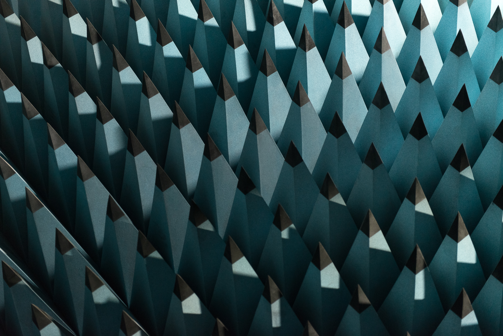 A photo of some radio-wave insulating foam. The foam is formed in to tall pointy pyramids with pale blue bases and black tips. The pyramids are arranged in a rigid grid - as if the entire floor were spikey.