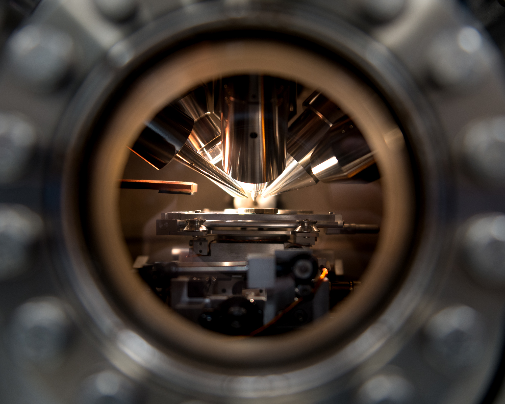 A macro photo through a circular window looking at several sensing instruments pointing at a coin.