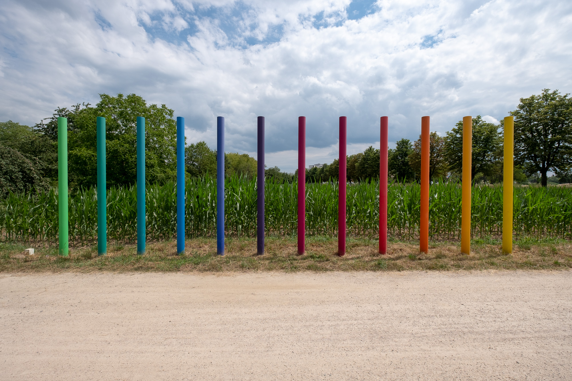 A photo of a sculpture in a field. It consists of 12 poles emerging from the earth and pointing upwards. They're arranged in a row, and are coloured like a rainbow, from green to blue, red, and yellow.