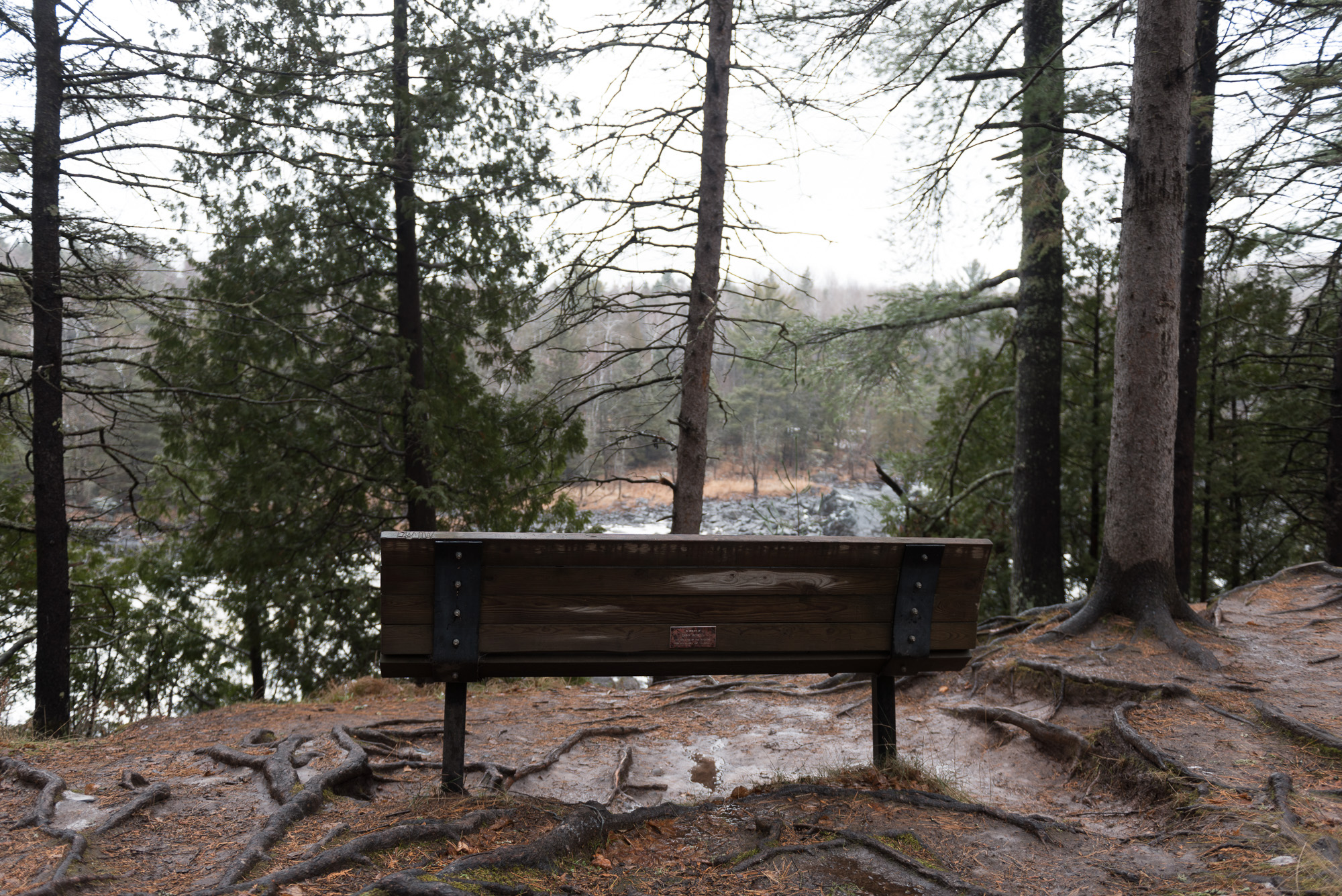 A photo from behind of a park bench overlooking a snowy river.