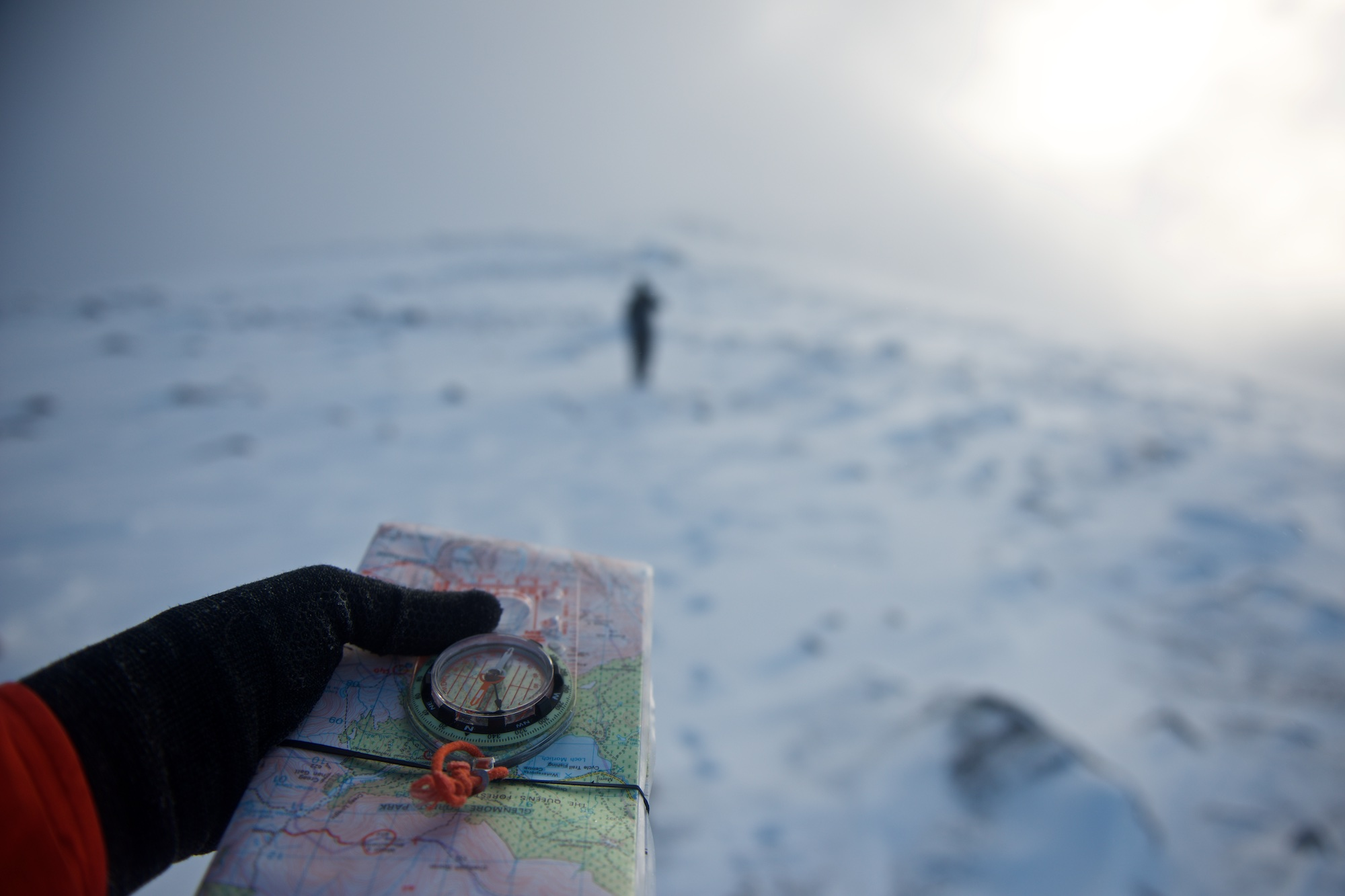 A hand in the foreground holds a compass and map. In the background is a figure walking away. The compass is pointing towards the figure.