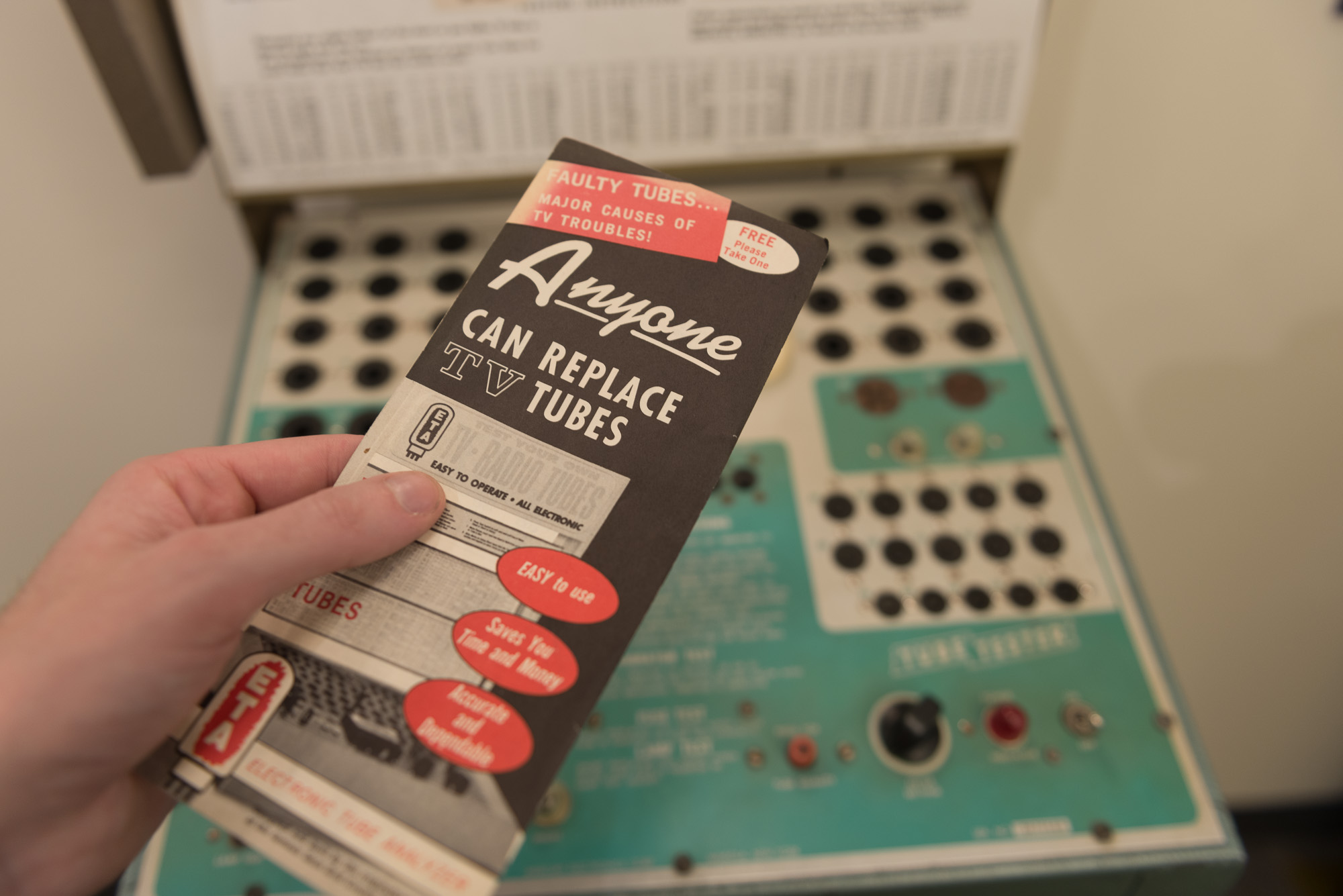 A vintage electronics pamphlet held in a hand above a piece of vintage electrical equipment. The pamphlet reads 'Anyone can replace TV tubes'.
