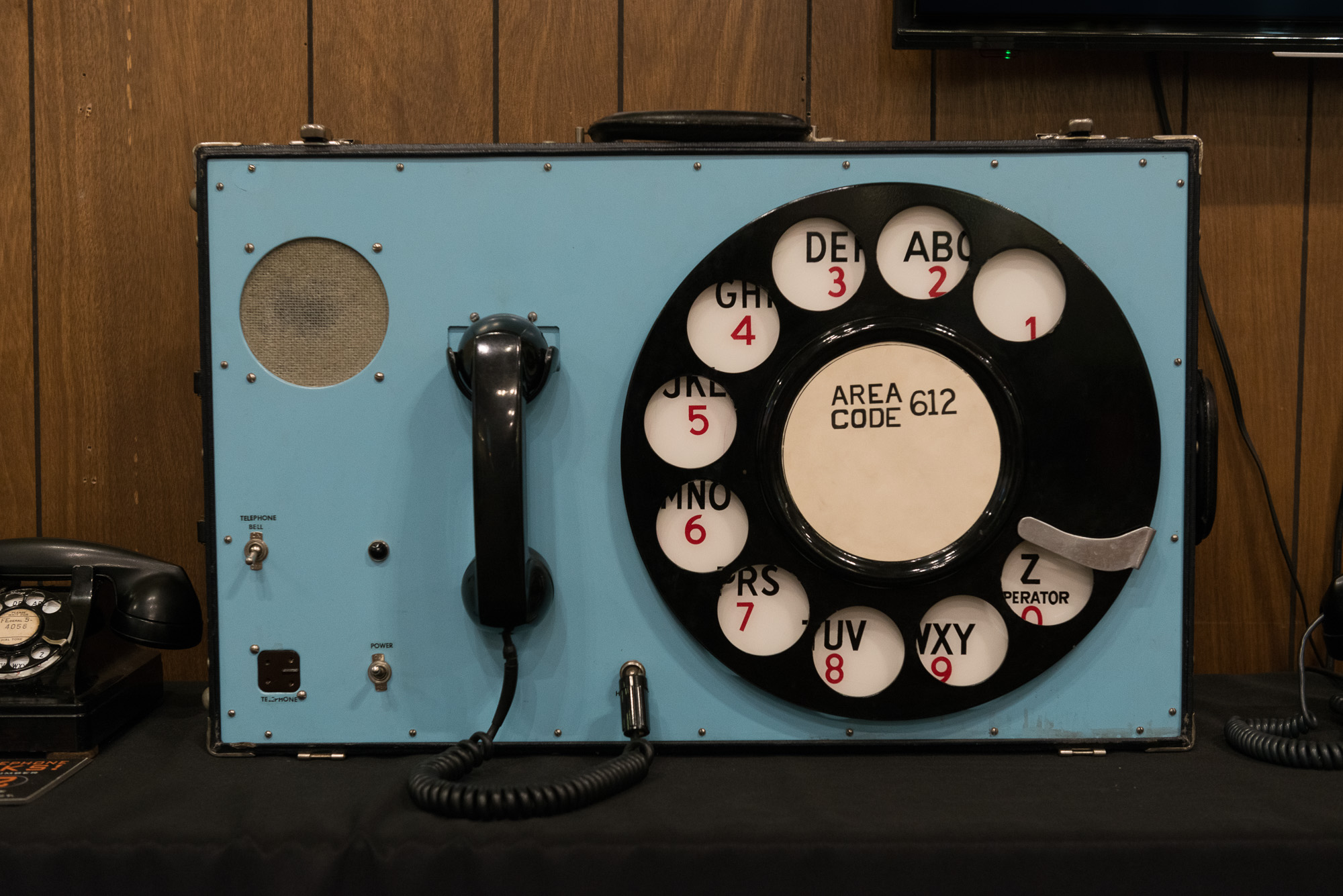 A large vintage suitcase telephone. It has a standard receiver, but the rotary dialer is much larger than normal. The whole unit is about the size of a small suitcase and has a handle on the top. It looks comically large.