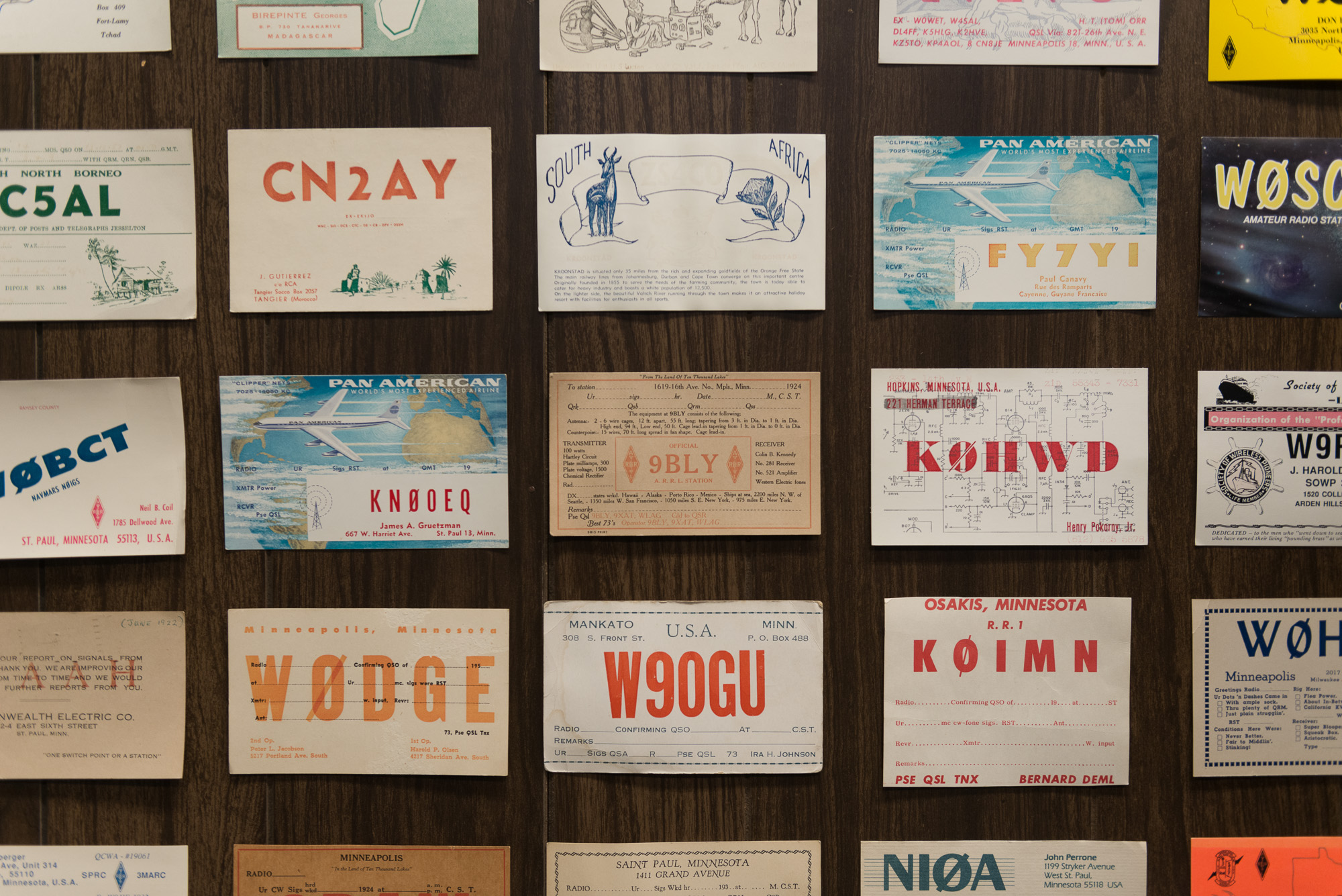 A grid of radio postcards on a wall. The cards are evenly spaced, but each very differently designed. Some have bold typography featuring 5 letter codes. Others depict animals / planes / local scenes.
