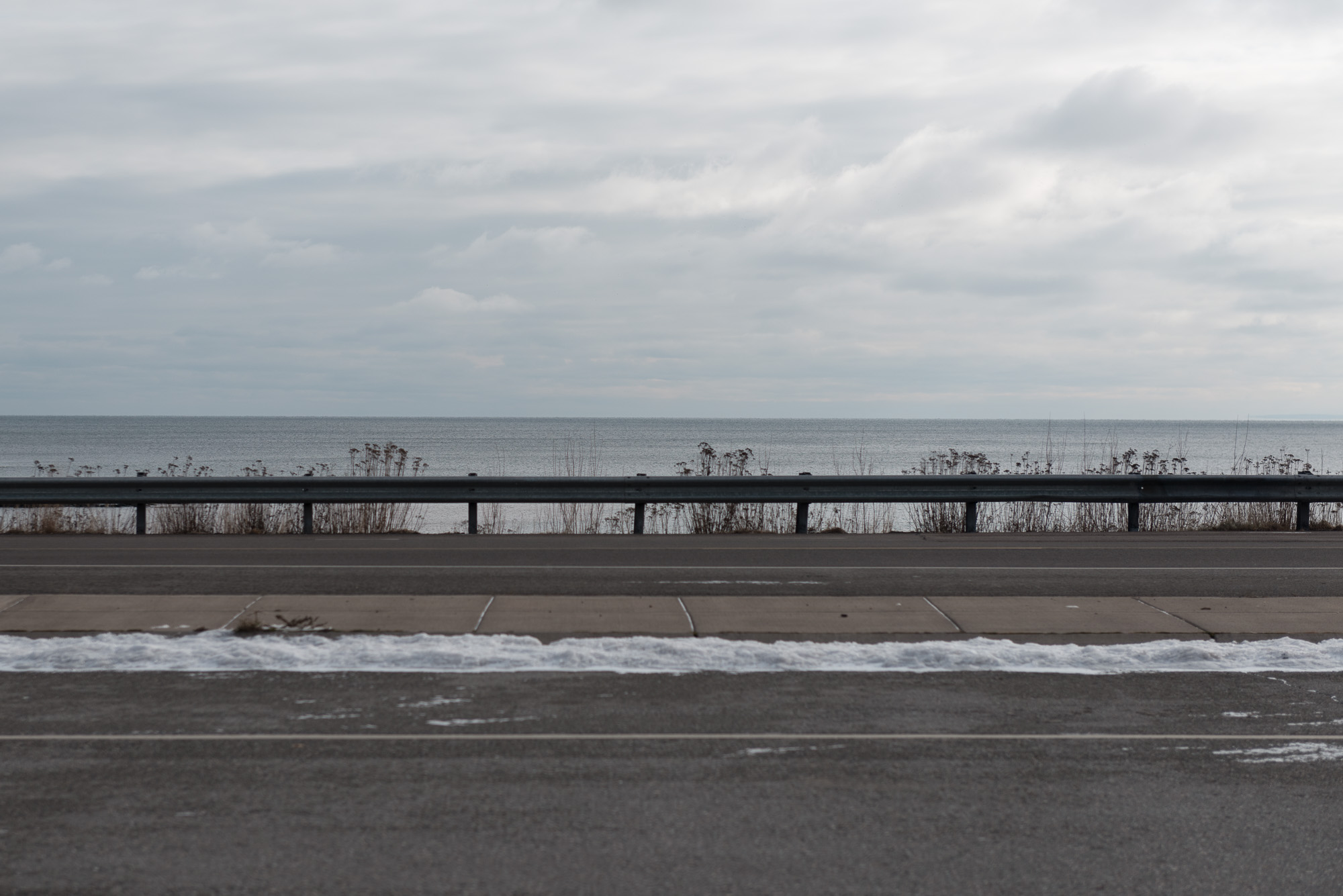 A photo from the side of a highway looking over the side. Lake Superior is in the background.