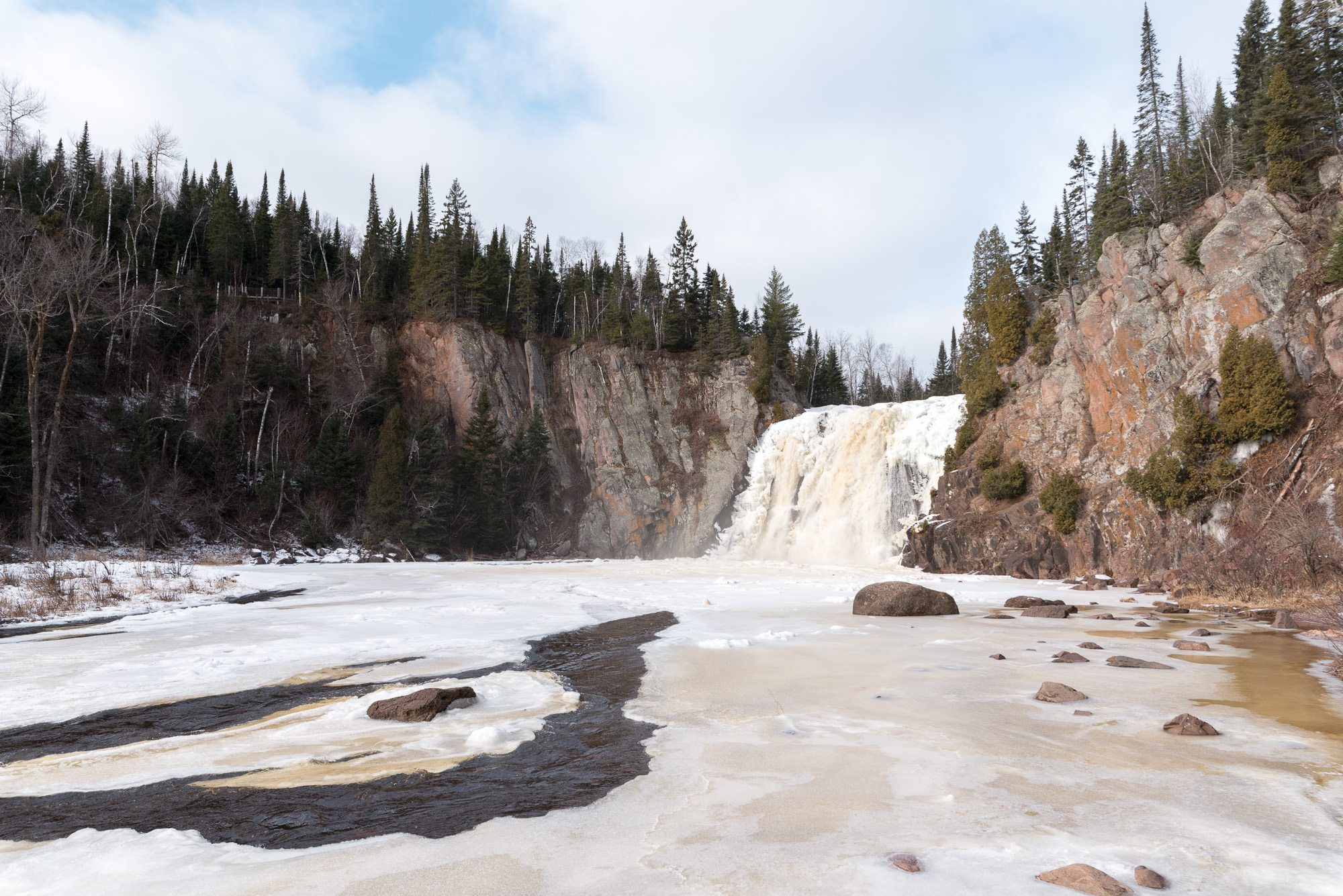A photo of High Falls taken from the pool at it's base. The water is partially frozen over.