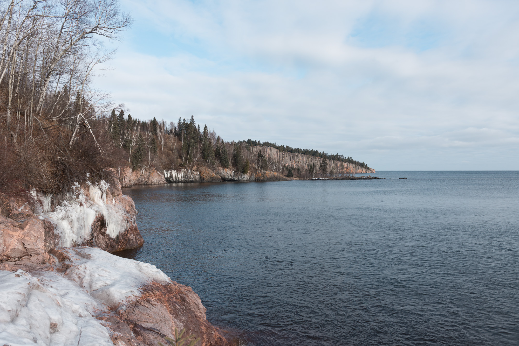 A photo from the shore of Lake Superior, looking East. There's snowy frocks on the right.