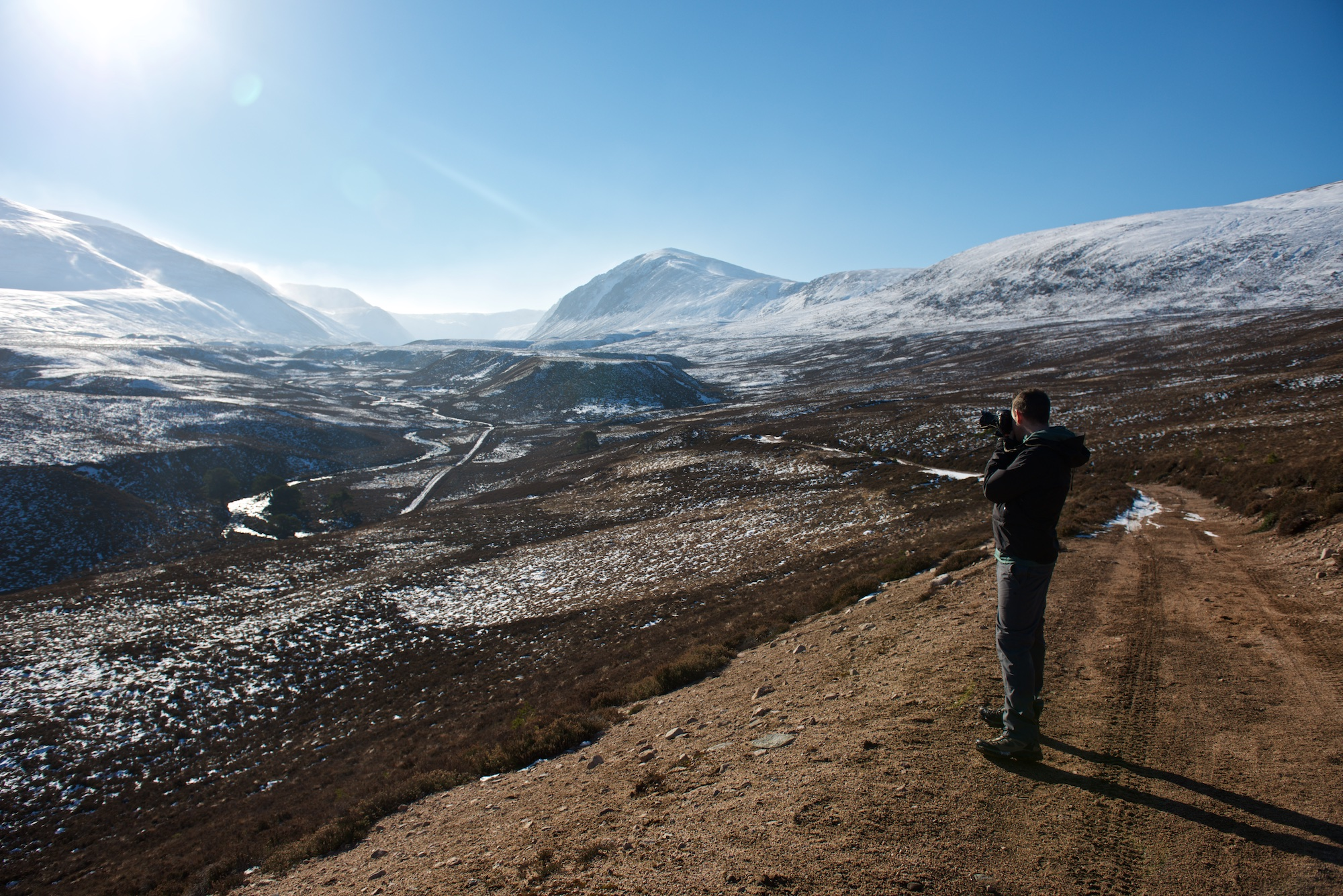 Chris stands on a high path taking a photo of the Gleann Eanaich valley in bright sunlight.