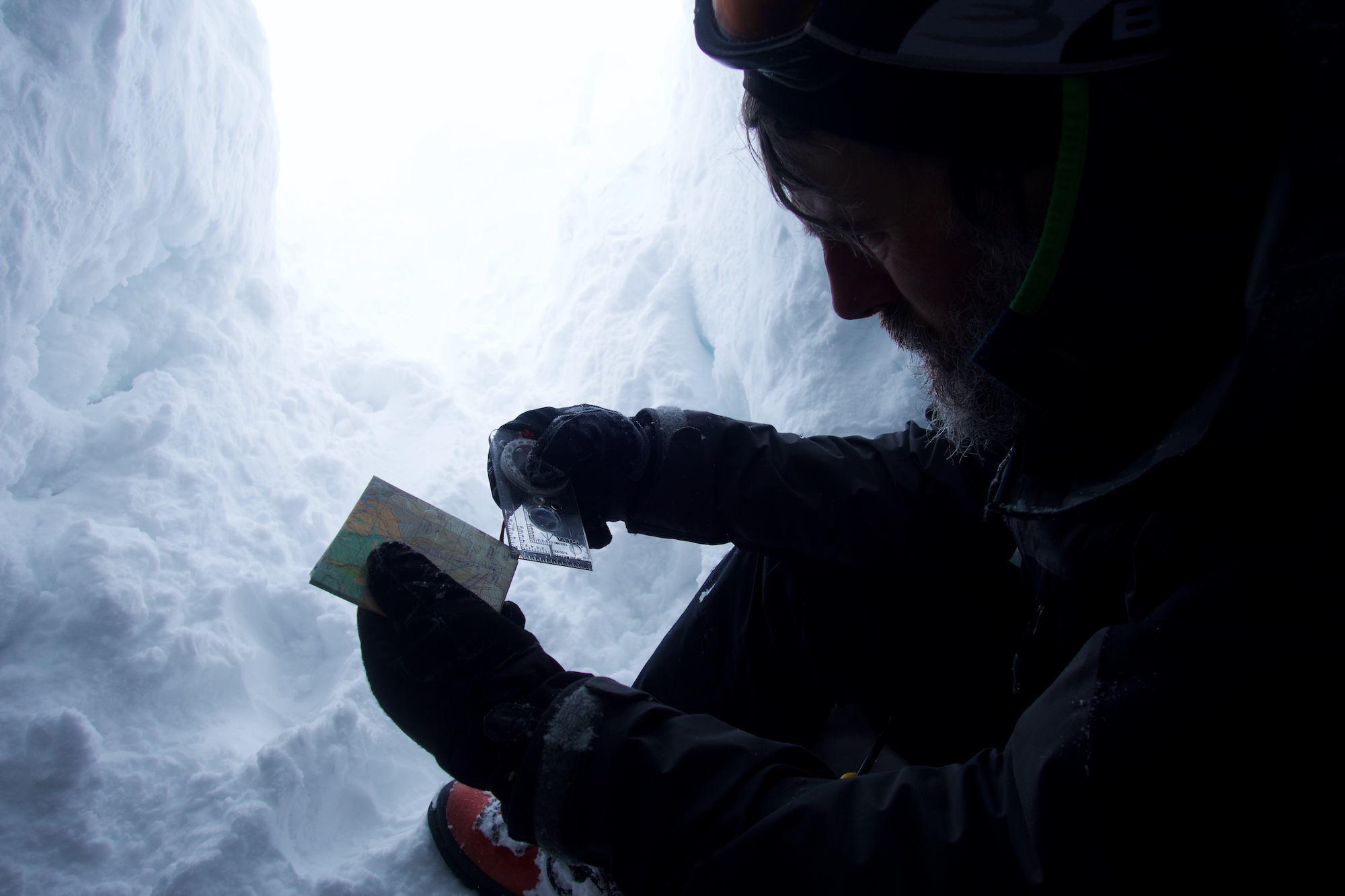A man uses the corner of a compass to look at a map. He's sat inside a snow hole.