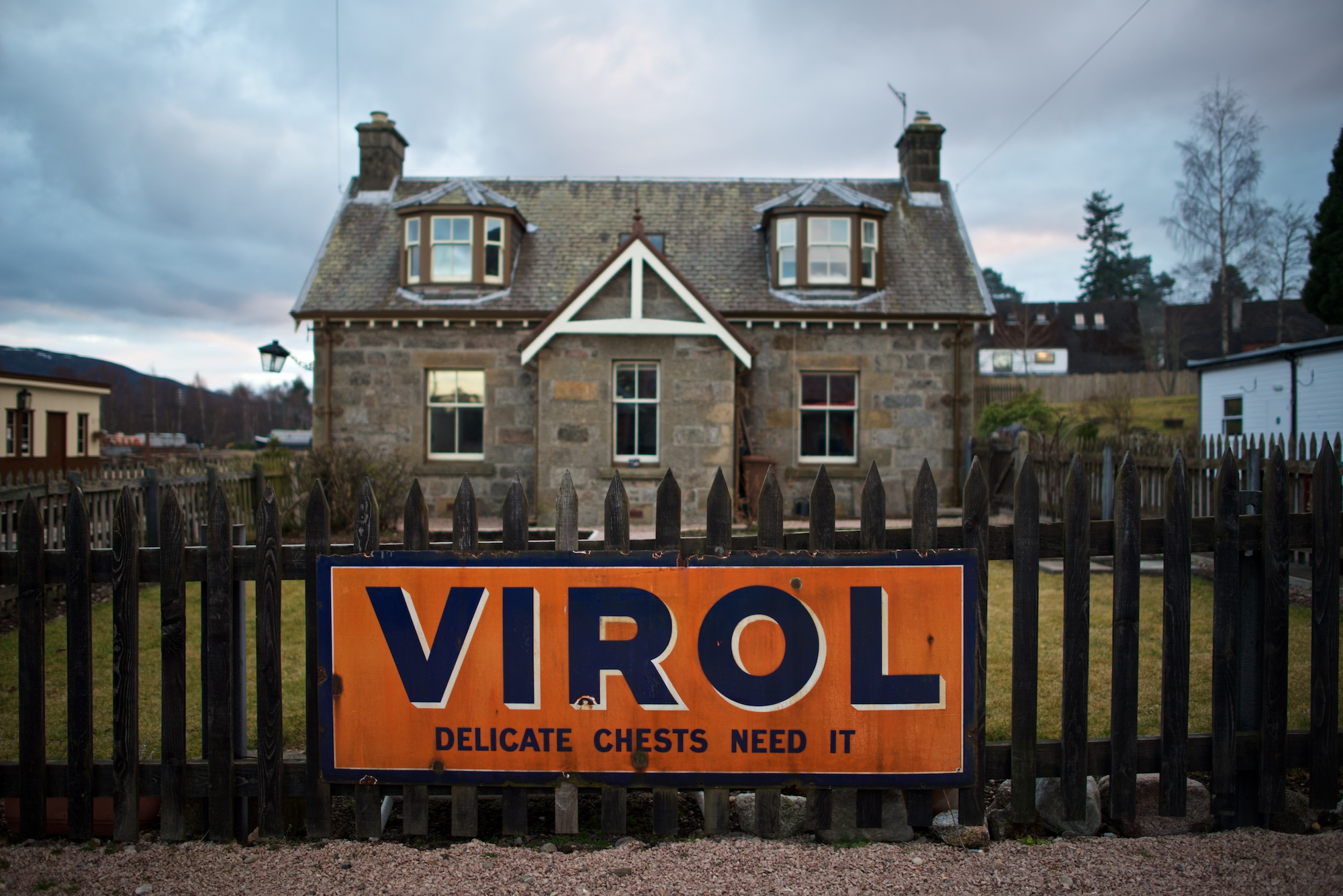 Facing straight on to a large orange sign in front of a cottage. The sign is written in large uppercase blue letters and reads 'VIROL'.