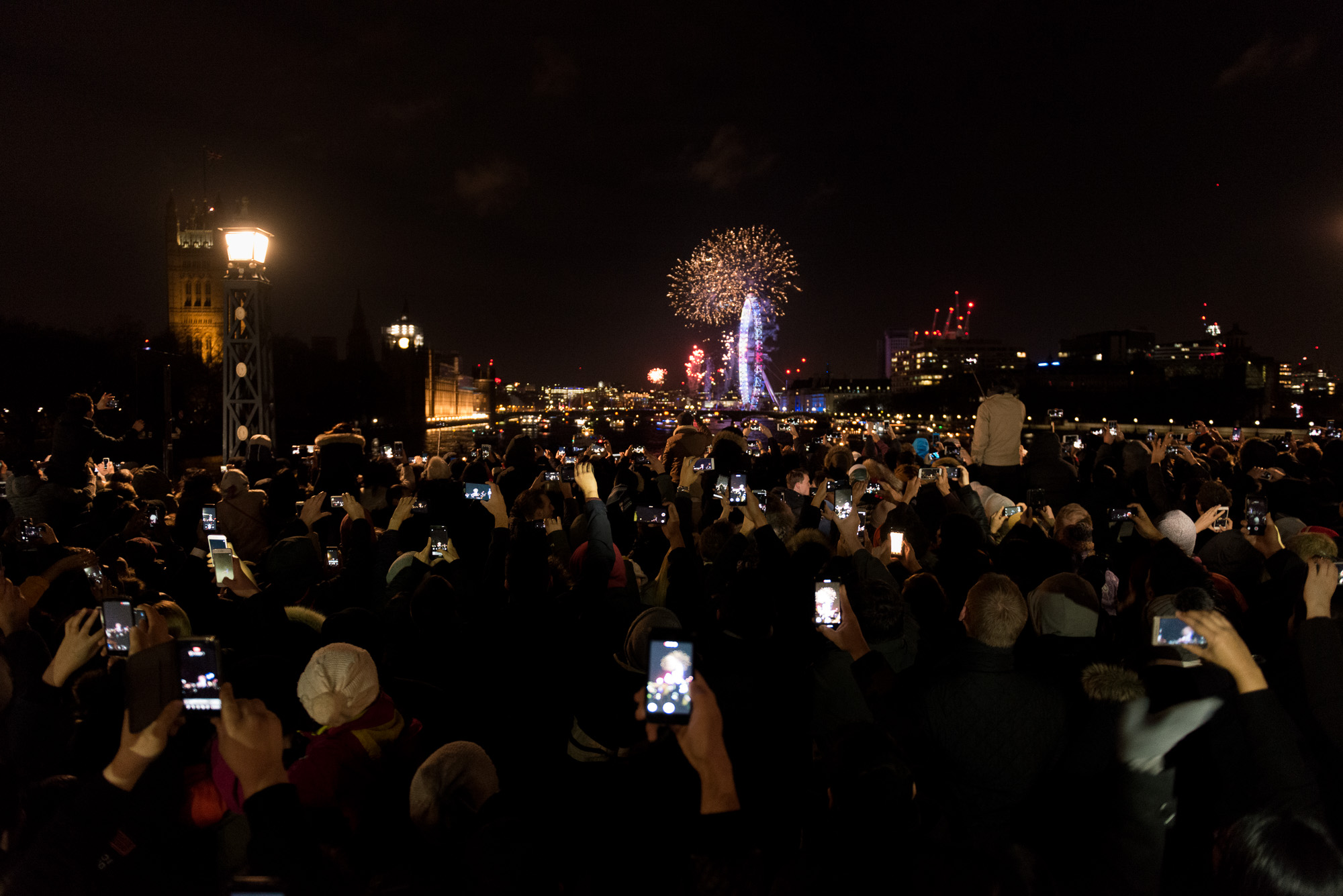A crowd on Lambeth Bridge watch the New Years fireworks display over the London Eye. Many are holding phones in the air taking photos.