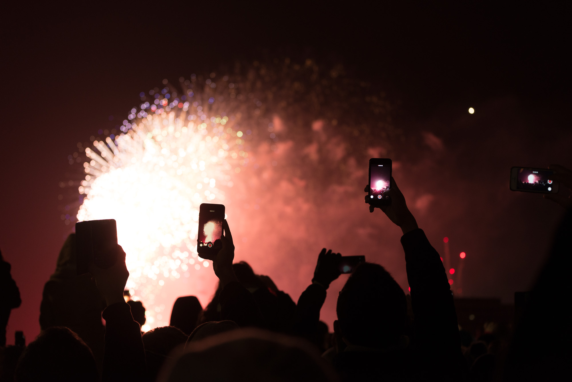 Four phones are held in the air taking photos and videos of fireworks in the distance.