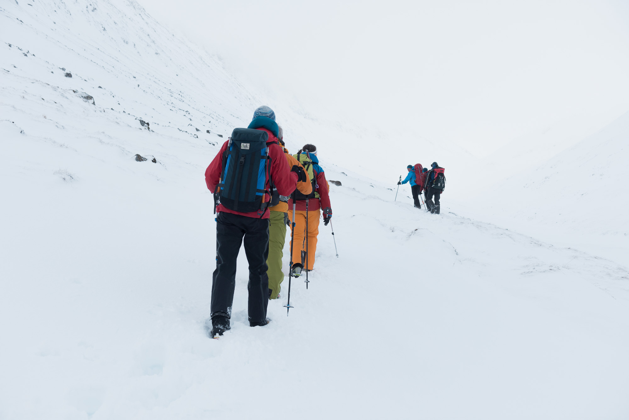 Two groups of climbers walk towards the horizon in snow. The sky is foggy / overcast and blending in with the ground. The climbers are all wearing brightly coloured clothing.
