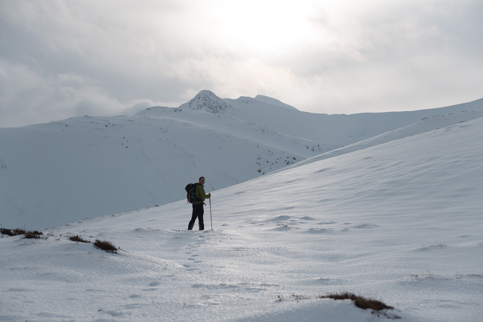Chris stands at the foot of a snowy coire with early morning sun ahead of him.